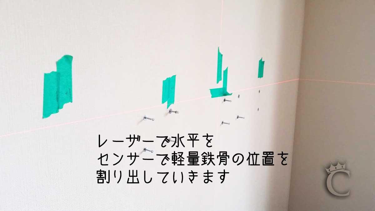 いくつかのセンサーを使用して壁の中を確認し、軽量鉄骨のあるラインにテープで目印をつけています